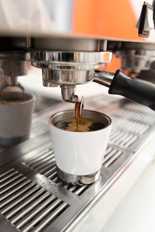 Zbliżenie ekspresu do kawy nalewającego kawę do filiżanki
