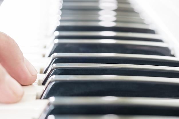 Zbliżenie elektronicznej klawiatury muzycznej i fortepianu do odtwarzania piosenki.