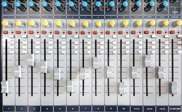 Zbliżenie elementów sterujących miksera audio.