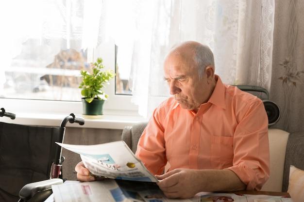 Zbliżenie emeryt siedzący i czytający wiadomości w tabloidzie podczas odpoczynku w mieszkaniu w pobliżu okna.