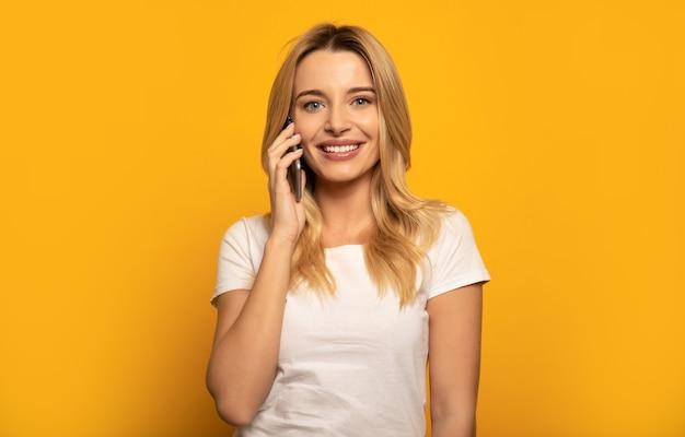 Zbliżenie enigmatycznej kobiety, która uśmiecha się patrząc w prawy górny róg i rozmawia przez telefon