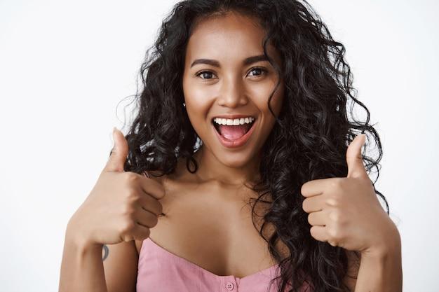 Zbliżenie entuzjastyczna i charyzmatyczna, przystojna dziewczyna wygląda optymistycznie, pokazuje gest kciuka w górę i szeroko się uśmiecha, zatwierdza świetny plan, zachęca przyjaciela, biała ściana