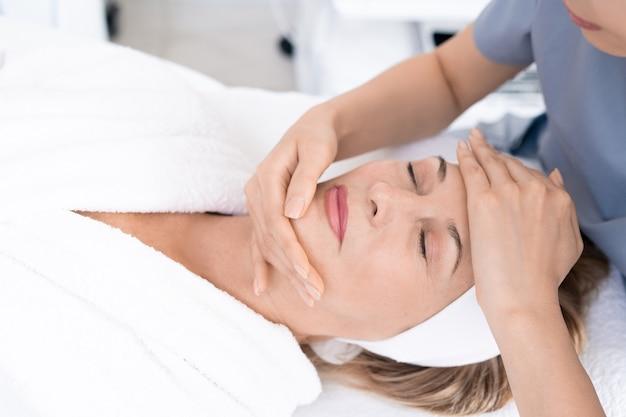 Zbliżenie estetycznej profesjonalnej rzeźbienia twarzy dojrzałej kobiety z masażem, zrelaksowanej kobiety korzystającej z zabiegu kosmetycznego