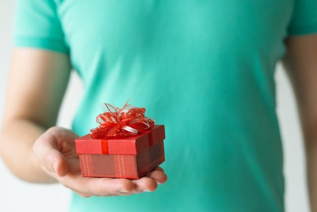 Zbliżenie facet trzyma małego czerwonego prezenta pudełko na palmie