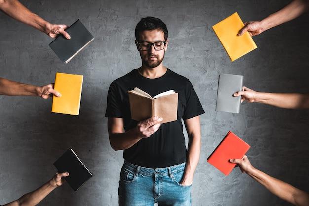 Zbliżenie facet w czarnej koszulce gospodarstwa książki na na białym tle szarej ścianie