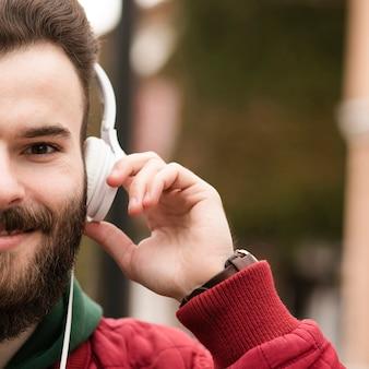 Zbliżenie facet ze słuchawkami i brodą
