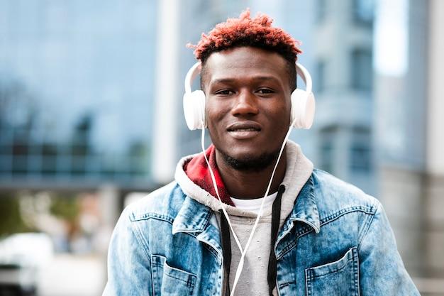 Zbliżenie facet ze słuchawkami i dżinsową kurtką