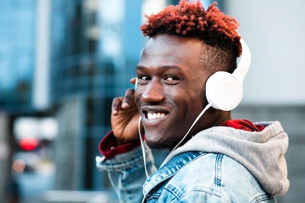 Zbliżenie facet ze słuchawkami i szeroki uśmiech