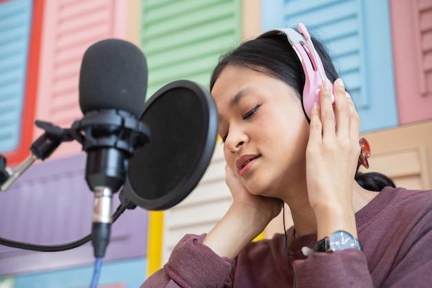 Zbliżenie fajnej azjatyckiej dziewczyny słuchającej w słuchawkach podczas podcastu