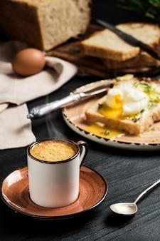 Zbliżenie: filiżanka kawy espresso z rosnącą parą na czarnym drewnianym stole. na rozmytej ścianie jajko na miękko (w koszulce) w kromce chleba, z maślanką i ziołami. pomysł na śniadanie