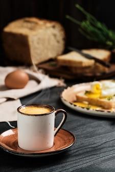 Zbliżenie: filiżanka kawy espresso z rosnącą parą na czarnym drewnianym stole
