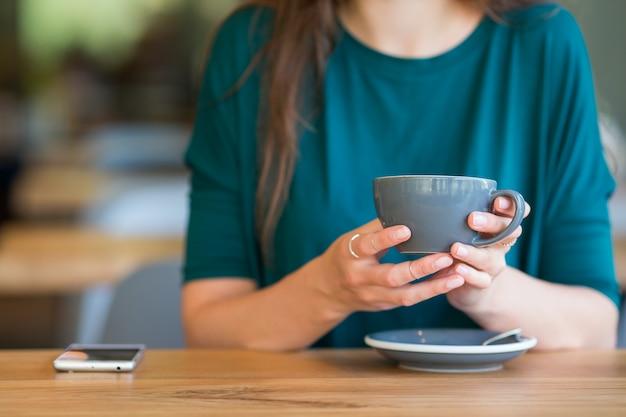 Zbliżenie filiżanka kawy. młoda kobieta w kawiarni na świeżym powietrzu
