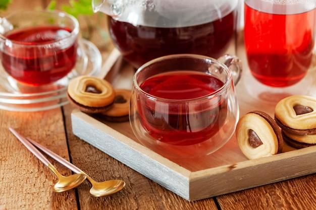 Zbliżenie filiżankę gorącej aromatycznej herbaty owocowej i ciasteczek w kształcie serca