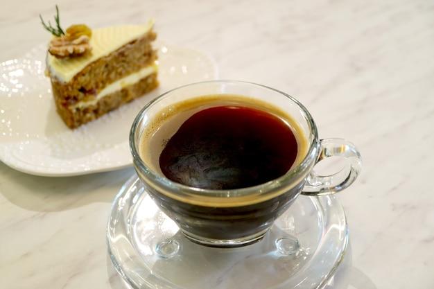 Zbliżenie filiżankę gorącej kawy z rozmytym domowym ciastem marchewkowym w tle