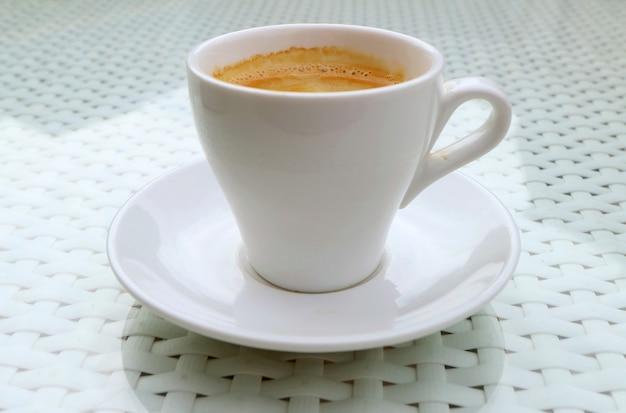Zbliżenie filiżankę gorącej spienionej kawy na białym stole