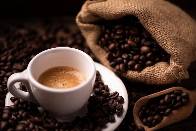 Zbliżenie filiżanki kawy nad ciemnymi palonymi ziarnami kawy