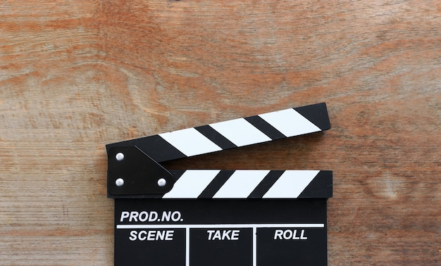 Zbliżenie filmu clapper deska na drewno stole z miękką ostrością i nadmiernym światłem w tle