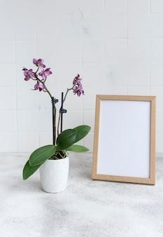 Zbliżenie fioletowej orchidei phalaenopsis w doniczce i makiety ramki plakatowej na stole