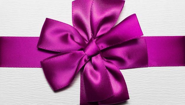 Zbliżenie fioletowej wstążki do pakowania w kształcie łuku na białe pudełko