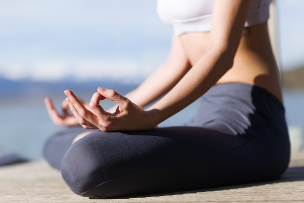Zbliżenie fit i sportowy młoda kobieta robi joga nad jeziorem.