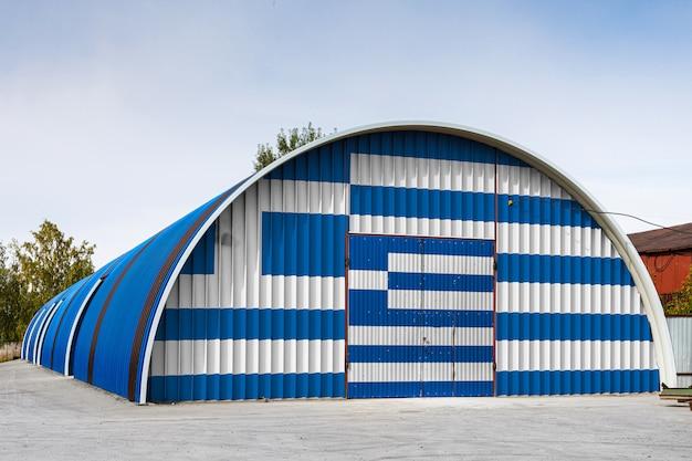 Zbliżenie flagi narodowej grecji malowane na metalowej ścianie dużego magazynu zamkniętego terytorium przeciw błękitne niebo. koncepcja przechowywania towarów, wejście do zamkniętego obszaru, logistyka
