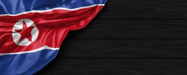 Zbliżenie flagi stanów zjednoczonych korei północnej na czarnym drewnianym tle renderowania 3d