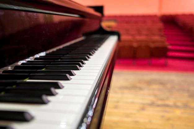 Zbliżenie fortepianu przed przestrzenią koncertową
