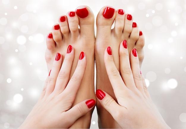 Zbliżenie fotografia pięknych żeńskich stóp z pedicure i rąk z manicure