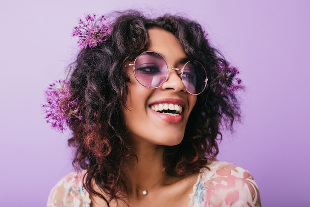 Zbliżenie fotografii wesołej afrykańskiej damy z kwiatami we włosach. kryty strzał śmiejąc się czarna dziewczyna na białym tle.