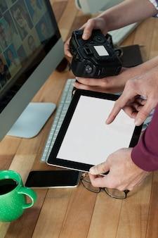 Zbliżenie fotografów pracujących przy biurku
