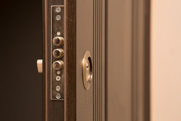 Zbliżenie fragment otwartych drzwi z zamkiem i dziurką od klucza