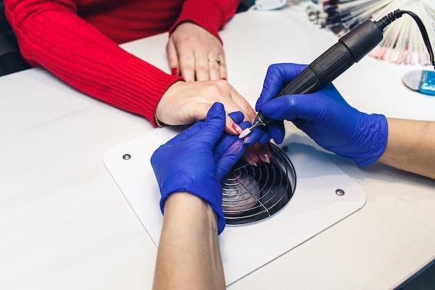 Zbliżenie frezowania paznokci w gabinecie kosmetycznym. kobieta dostaje manicure