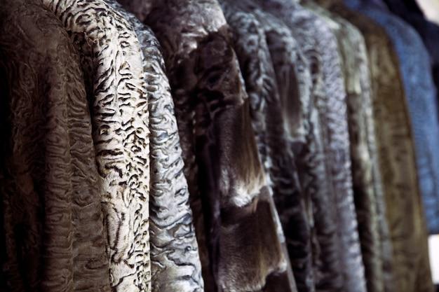 Zbliżenie futra z naturalnego futra astrachania w różnych kolorach: brązowym, szarym i czarnym, zawieszone w jednym rzędzie w sklepie