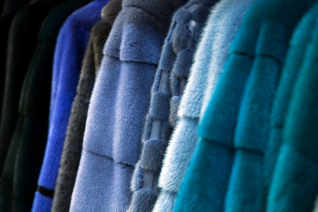Zbliżenie futra z naturalnego futra norek w różnych kolorach: szarym, niebieskim, zielonym i czarnym wisi w jednym rzędzie w sklepie