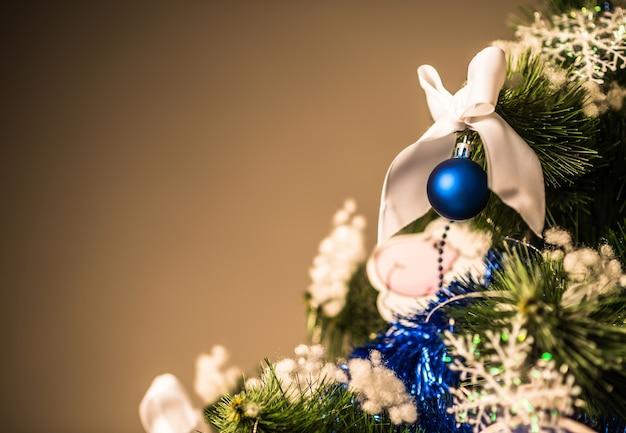 Zbliżenie: gałąź choinki z zabawkami na ciemnym tle. koncepcja nowy rok i świąteczny nastrój na zakupy i rabaty. przestrzeń reklamowa