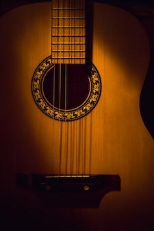 Zbliżenie gitary akustycznej w ciemności, oświetlone wiązką światła.