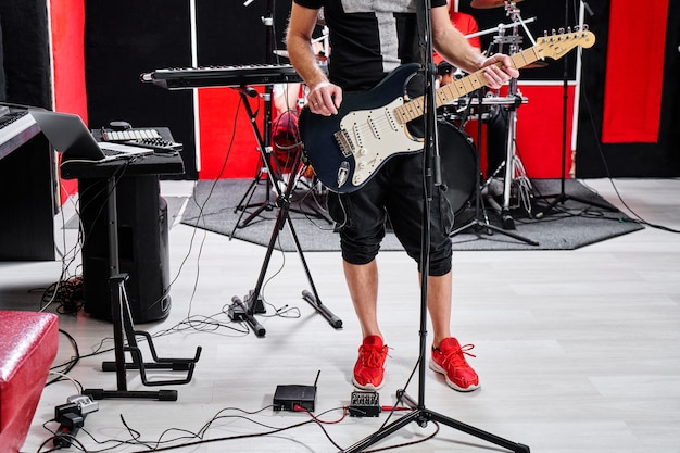 Zbliżenie gitarzysty zespołu muzycznego grającego na gitarze elektrycznej na tle bazy prób, bez twarzy
