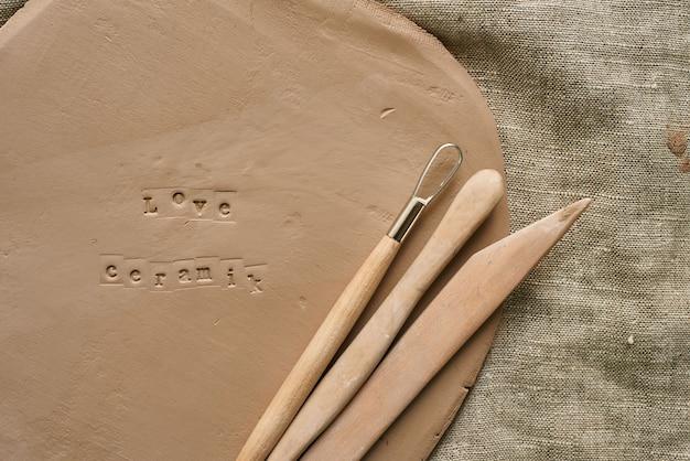Zbliżenie gliniana płyta z drewnianymi narzędziami do rękodzieła z nadrukiem love ceramic