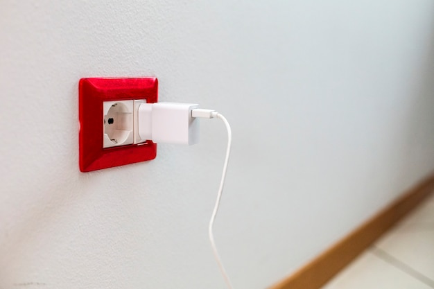 Zbliżenie gniazdka elektrycznego przymocowanego do ściany domu. ładowarka podłączona do gniazdka.