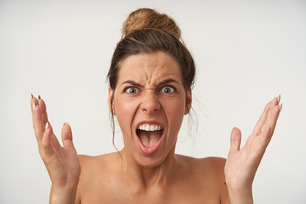 Zbliżenie gniewnej młodej uroczej kobiety pozującej z podniesionymi dłońmi, marszczącej brwi i krzyczącej z szeroko otwartymi ustami