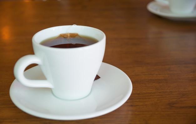 Zbliżenie gorąca herbaciana filiżanka na drewnianej stołu i kopii przestrzeni.