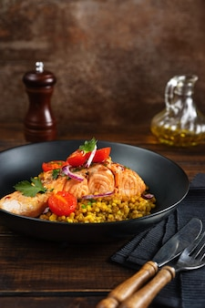 Zbliżenie gotowanego fileta z łososia z warzywami i kaszą gryczaną w czarnej płycie.