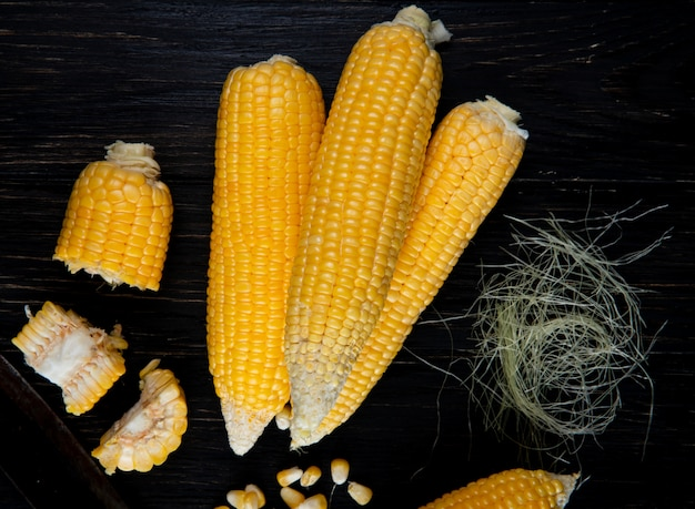 Zbliżenie gotowanych całych i ciętych kukurydzy z jedwabiem kukurydzianym na czarnej powierzchni
