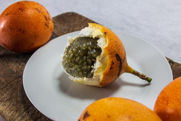 Zbliżenie granadilla owoc peruwiański o twardej skórce na porcelanowym talerzu i drewnianej desce