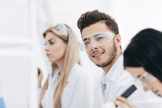 Zbliżenie. grupa młodych naukowców w laboratorium. nauka i zdrowie