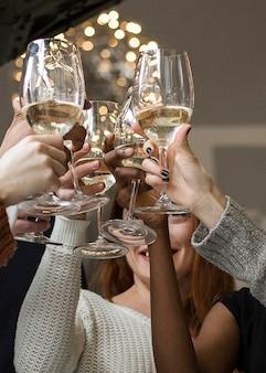 Zbliżenie grupa przyjaciół opiekania kieliszki do wina