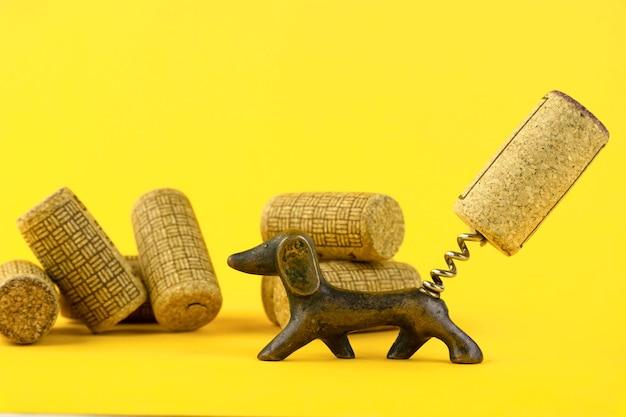 Zbliżenie grupy antycznych datowanych korków do wina i starego korkociągu, w postaci psa jamnika. na żółtym tle. skopiuj miejsce.