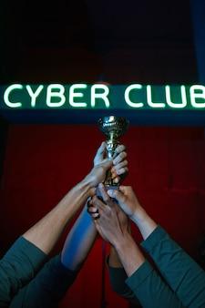Zbliżenie grupy graczy trzymających puchar razem oni wygrywają grę komputerową w konkursie zespołowym