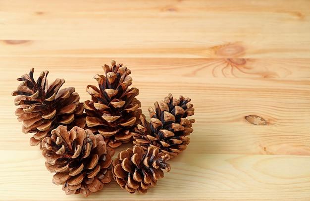 Zbliżenie grupy naturalnych suchych szyszek sosnowych na drewnianym tle