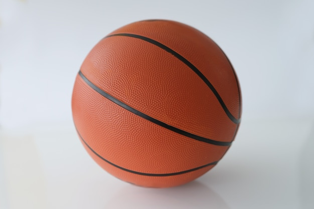 Zbliżenie gumowej piłki do koszykówki na białym tle